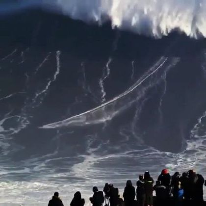 People watch and record scenes of men surfing on high waves