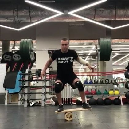 In gym, a man lifted heavy objects and balanced himself on the roller