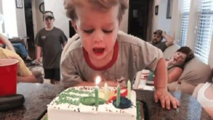 Everyone in family waits for child to blow a birthday cake in apartment's living room.