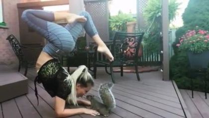 Girl practicing yoga next to squirrel in resort