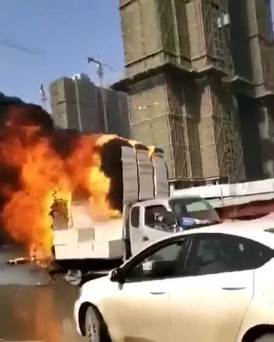 Man driving a burnt cargo truck in city